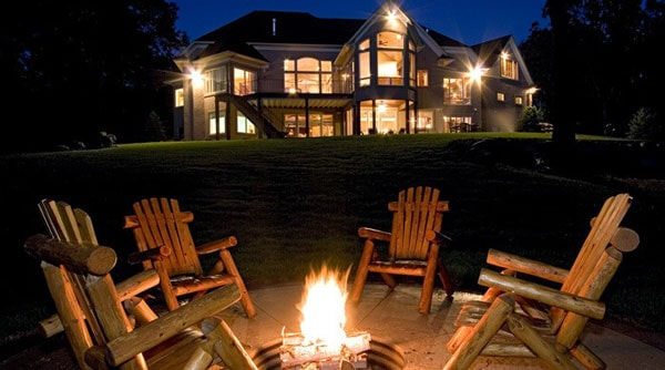 View of the house from the backyard with a fire pit surrounded by wooden armchairs.