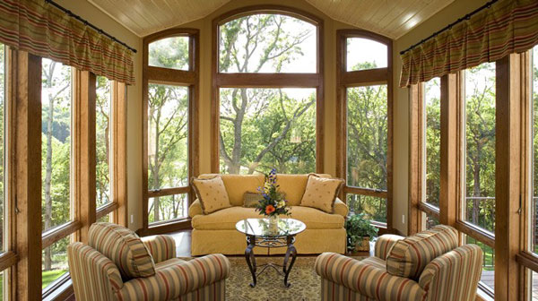The sunroom has a beige skirted sofa, striped armchairs, and a small round center table.
