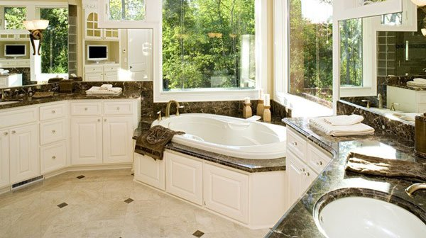 The primary bathroom has two vanities and a deep soaking tub placed under the bay window.