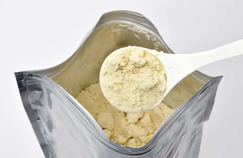 Scooping a tablespoon of soy protein powder from the package.