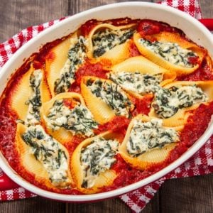 A freshly baked platter of spinach and three cheese stuffed pasta shells.