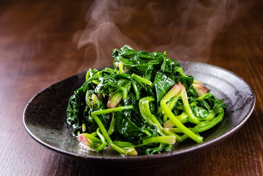 Steamed fried spinach in a black plate on wooden background.