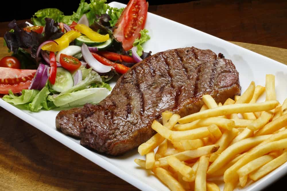 Steak with salad and fries on the side.
