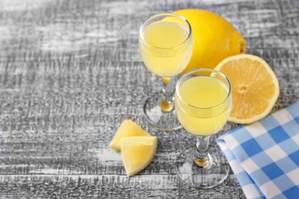 A couple of wine glasses of lemon juice beside sweet lemons.