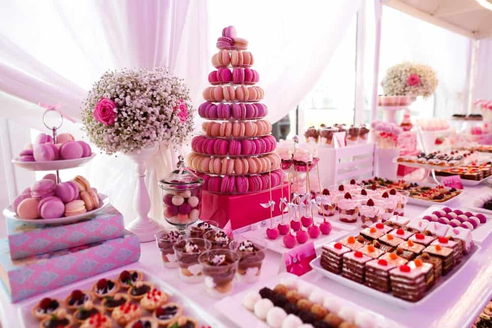 An assortment of pink-colored sweet treats on a skirted table.