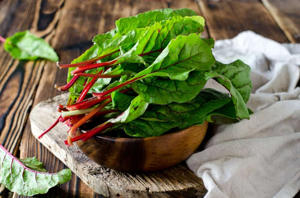 A bowl of Swiss chard on wooden chopping board and white cloth against the wood plank table.