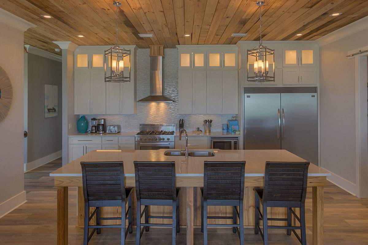 The kitchen has white cabinetry, slate appliances, and breakfast island well-lit by a pair of caged pendants.