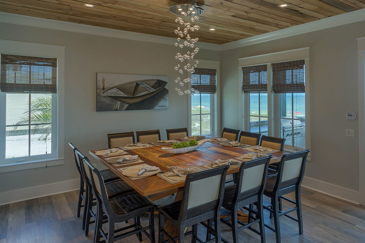 The dining room has a cascading chandelier, boat artwork, and a large wooden table surrounded by matching chairs.