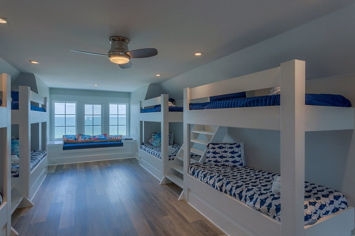 This bedroom is filled with custom bunk beds and a window seat.