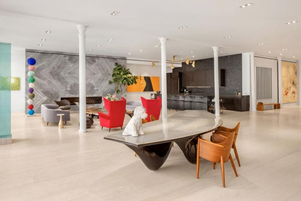 This is a look at the great room that houses the dining area with a modern table, living room with gray sofas and the kitchen with dark cabinets. Image courtesy of Toptenrealestatedeals.com.