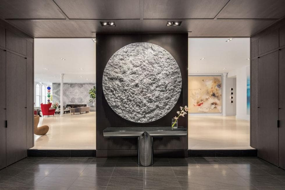 Upon entry of the loft, you are welcomed by this foyer that is adorned with a large stone disk artwork mounted above the console table. Image courtesy of Toptenrealestatedeals.com.
