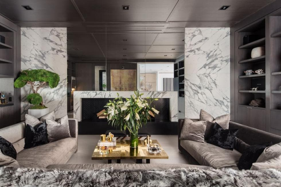 This is a closer look at the living room with white marble walls and gray sectional sofas paired with a coffee table. Image courtesy of Toptenrealestatedeals.com.