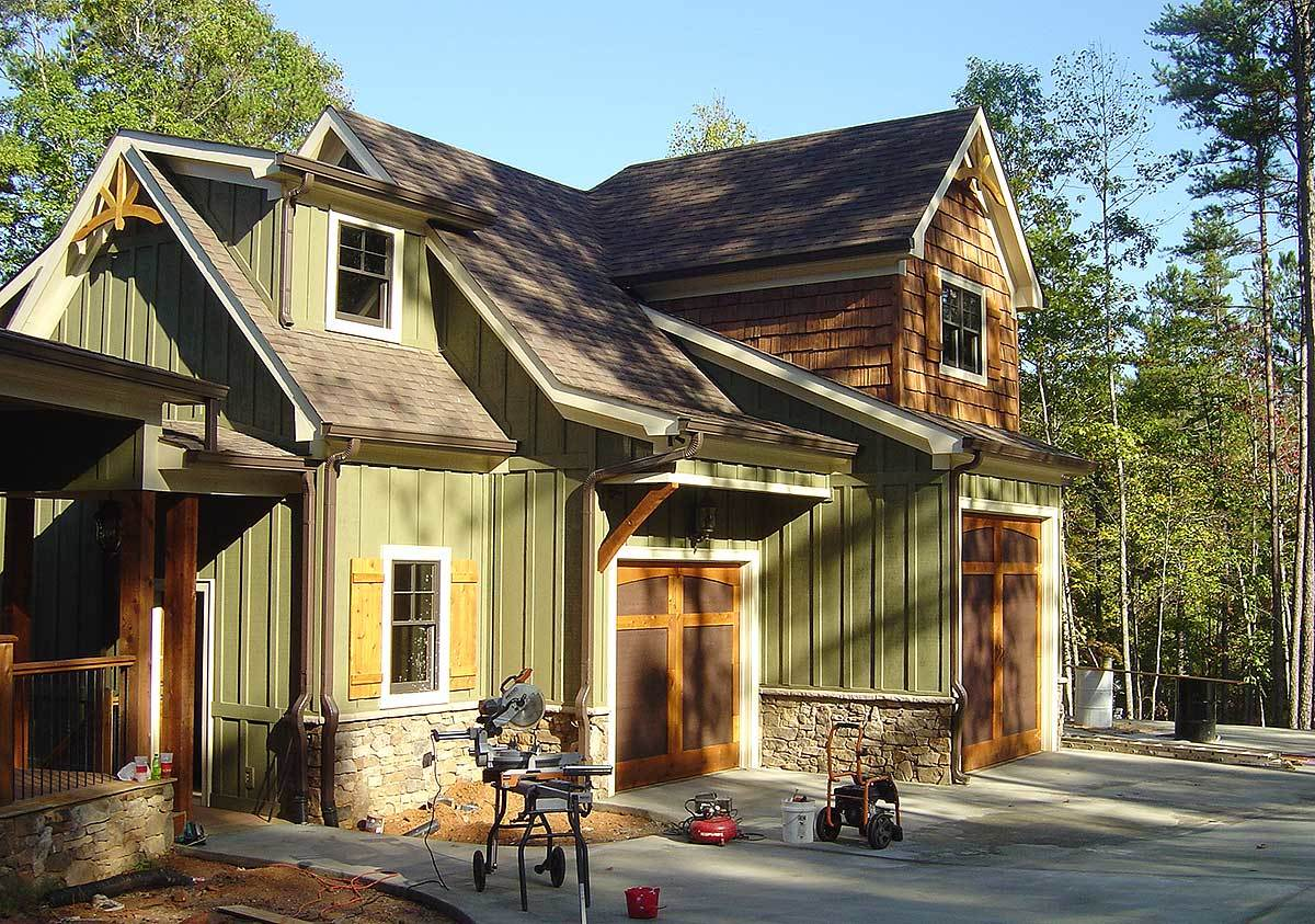 An angled view shows the vertical lap exterior siding and stone bases.