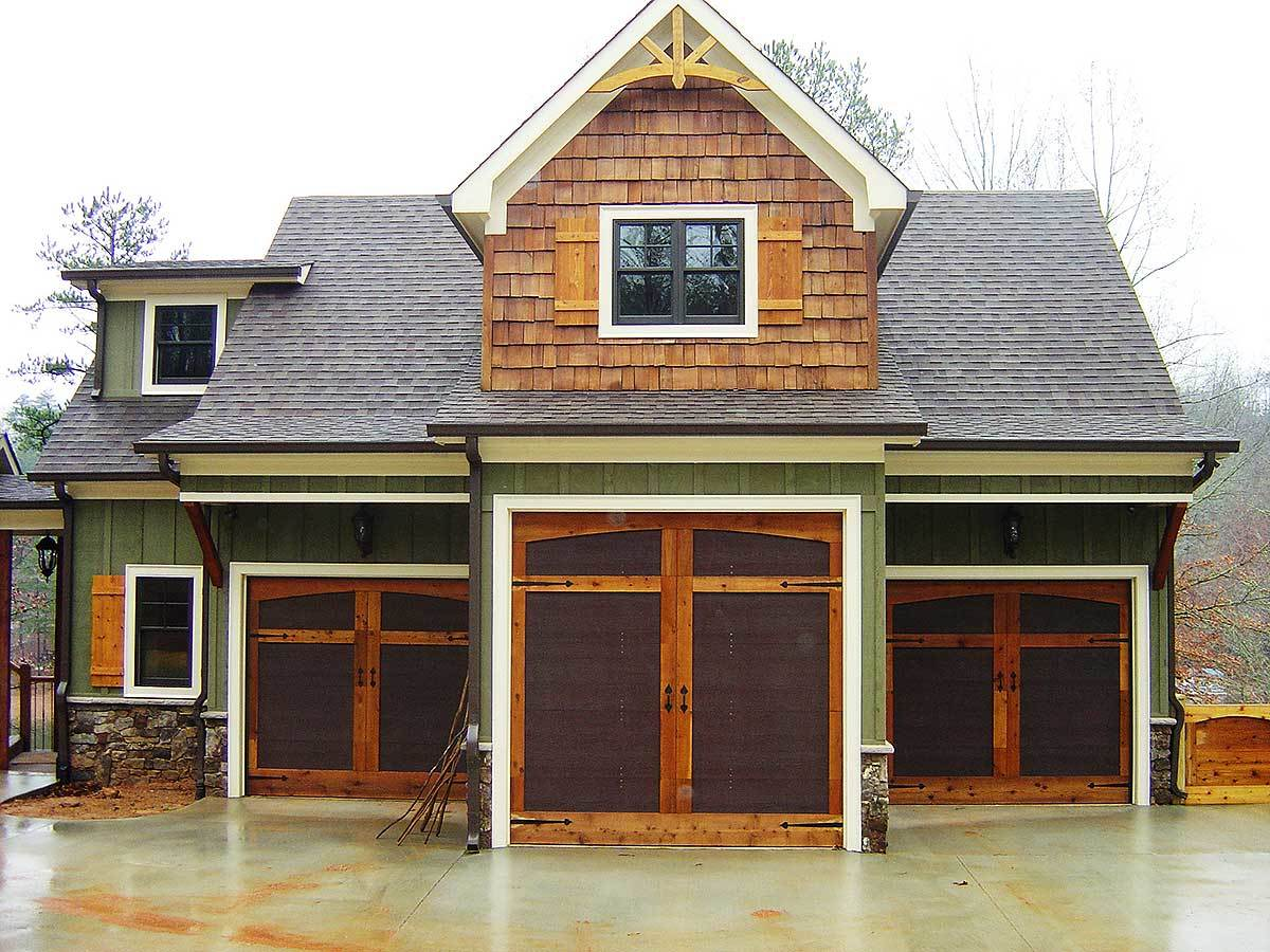 Front exterior view with a three-car garage and a large dormer window adorned with decorative wood trims.