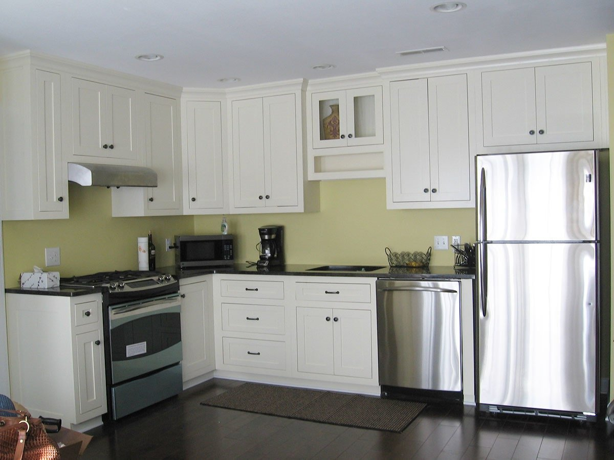 The kitchen is equipped with stainless steel appliances, undermount sink, black granite countertops, and white cabinets.