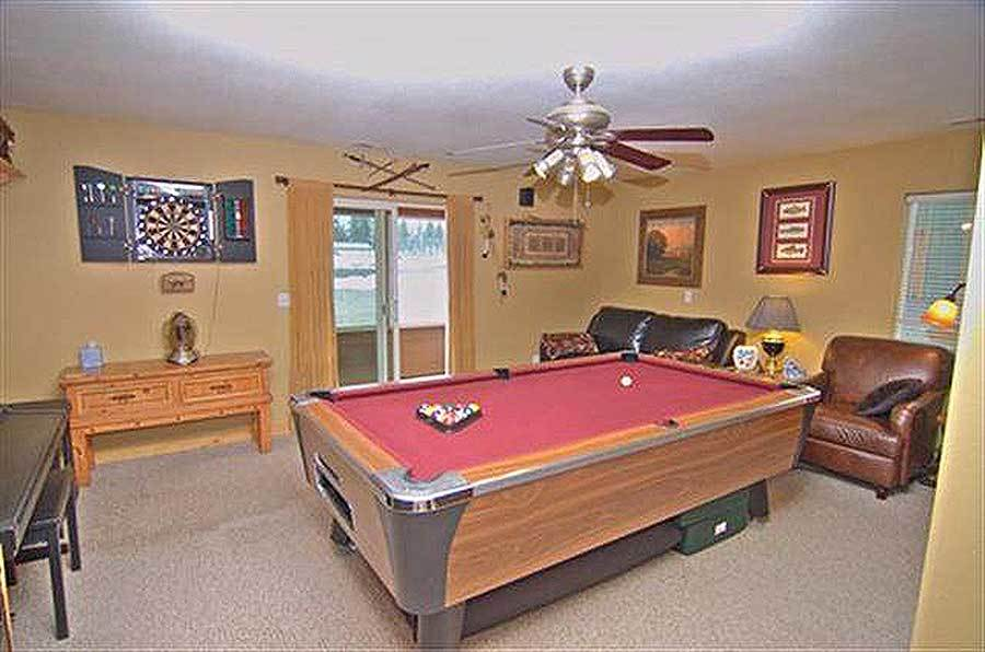 Game room with leather seats, wooden tables, and a billiard table placed under the ceiling fan.