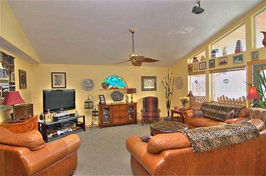 The living room offers a flatscreen TV, brown leather seats, and a brass fan hanging from the regular white ceiling.