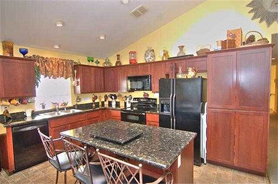 The kitchen is equipped with black appliances, granite countertops, wooden cabinets, and a breakfast island.