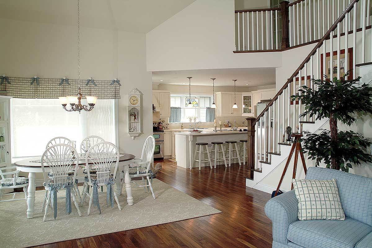 An open layout view showing the living area, kitchen, and dining room with round back chairs and oval dining table.