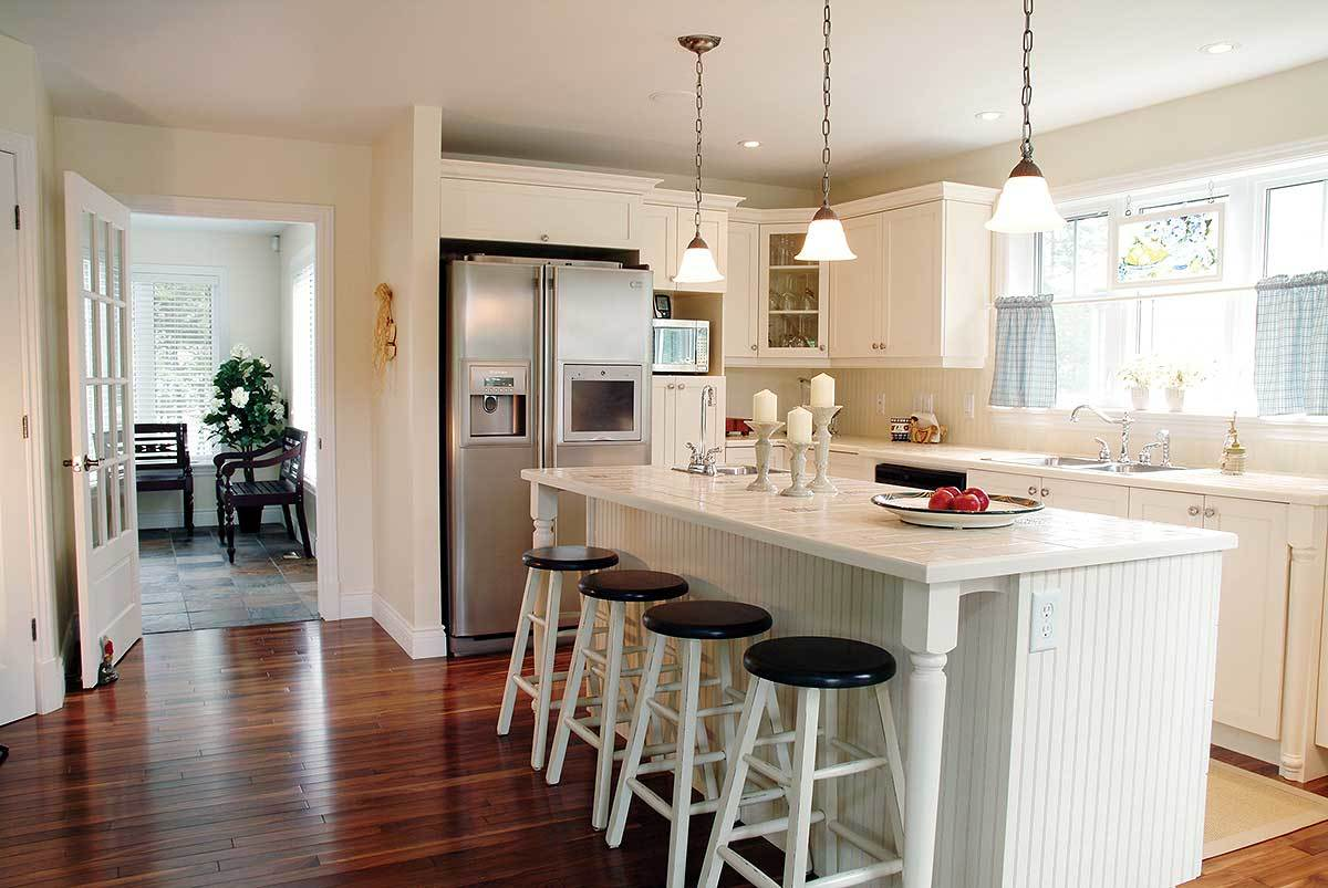 The kitchen has white cabinets, stainless steel appliances, and a beadboard island lined with round bar stools.