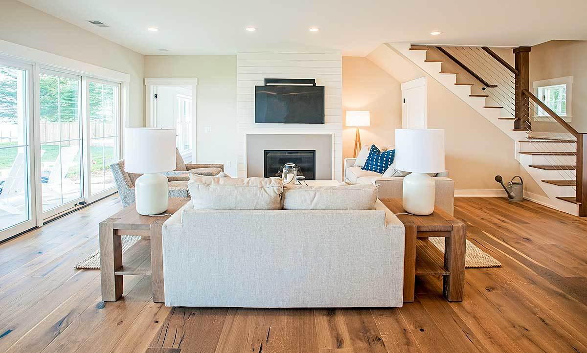 The living room has beige seats, wooden tables, and a glass-enclosed fireplace with a TV on top.