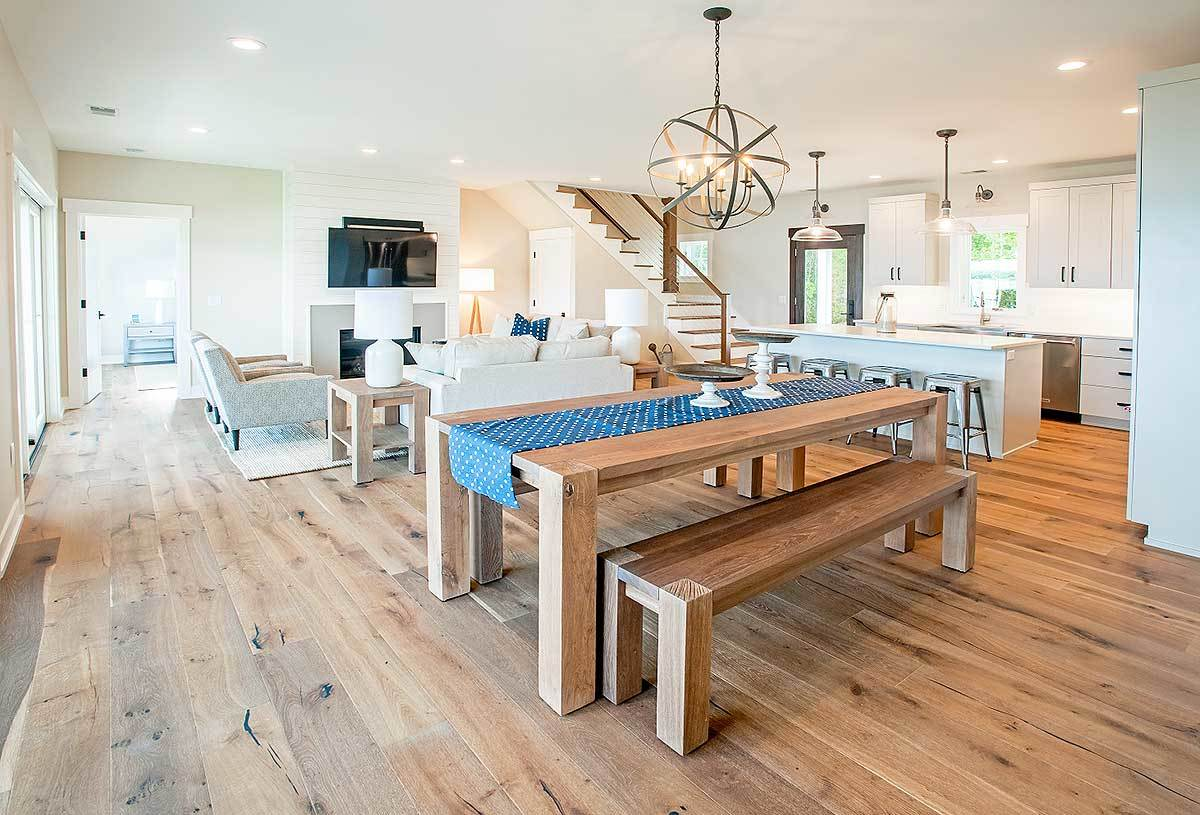 The dining area has a spherical chandelier, wooden benches, and a matching dining table lined with a blue dotted runner.