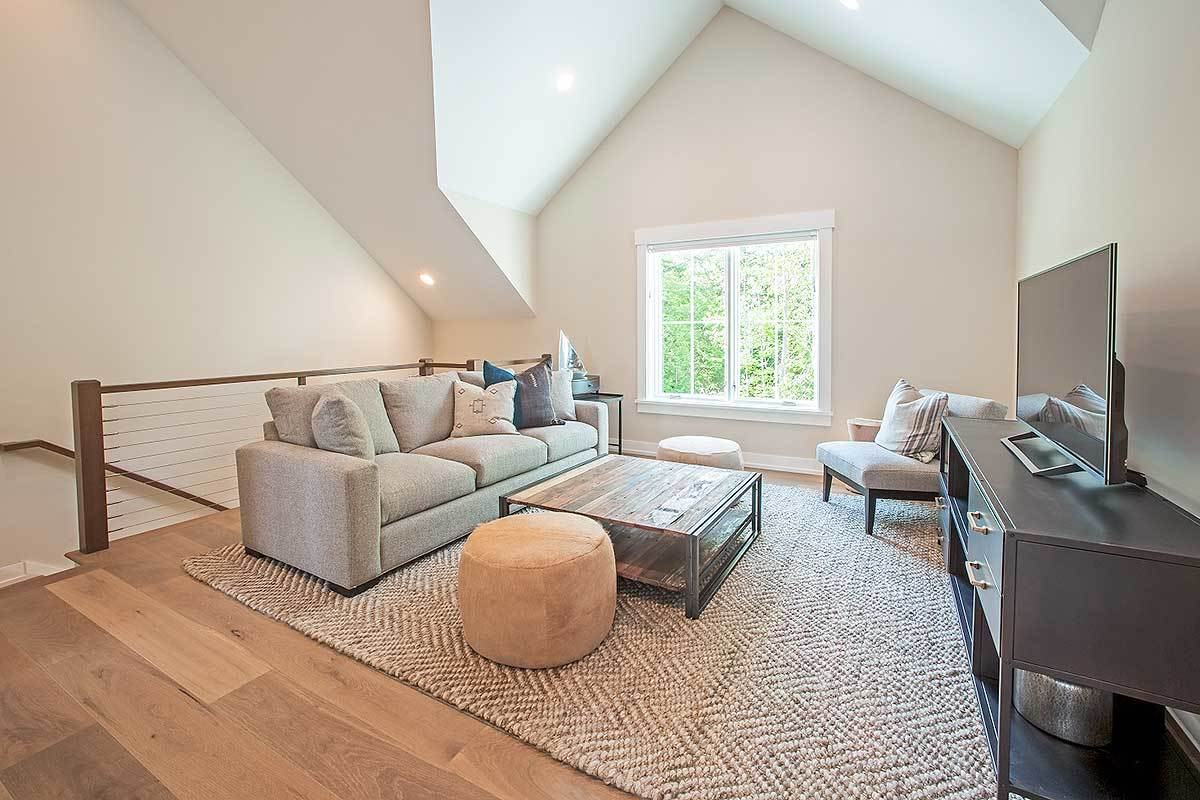 The loft is filled with gray sectional and chair, wooden coffee tables, velvet ottomans, and a flatscreen TV.