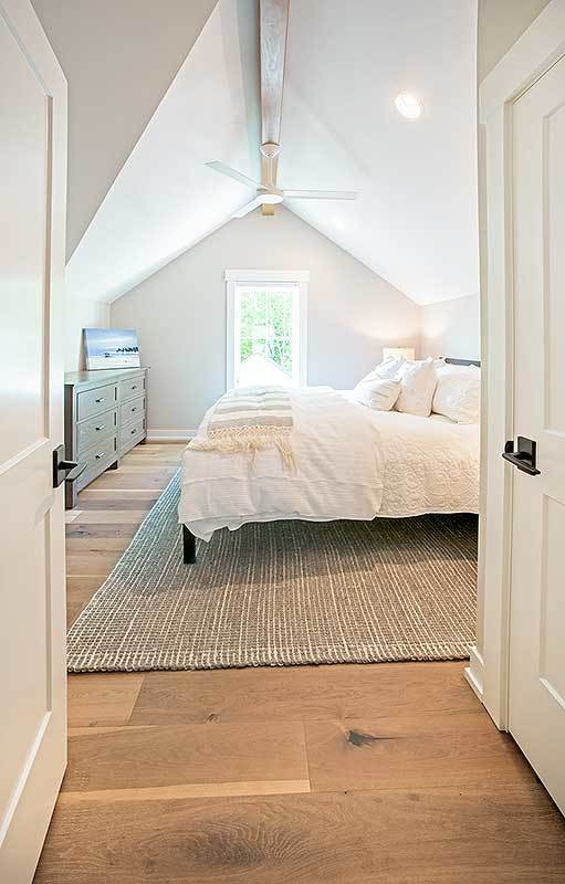 This bedroom has dark wood furnishings, a vaulted ceiling, and wide plank flooring topped by a jute area rug.