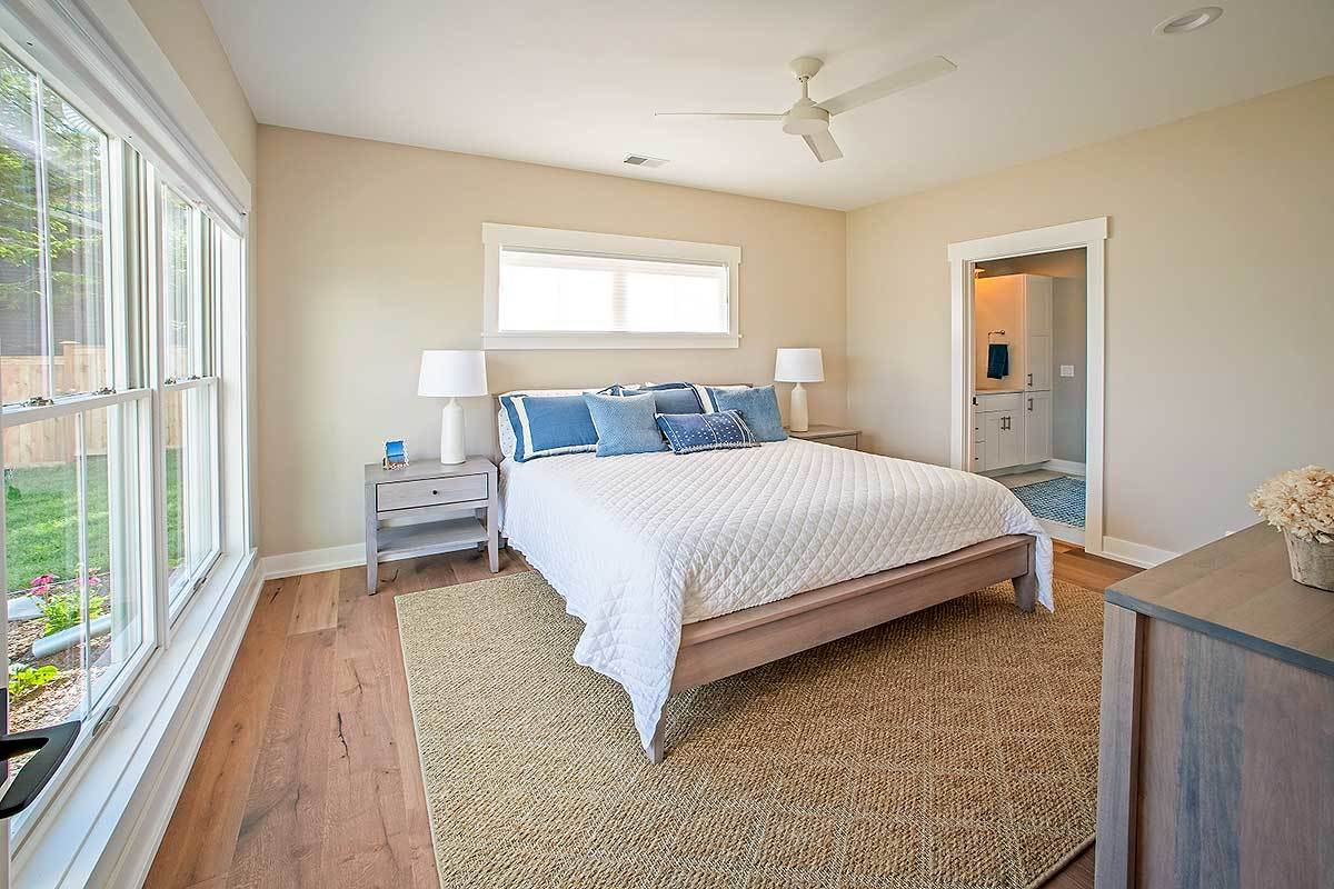 Primary bedroom with a private ensuite and a cozy wooden bed flanked by matching nightstands.