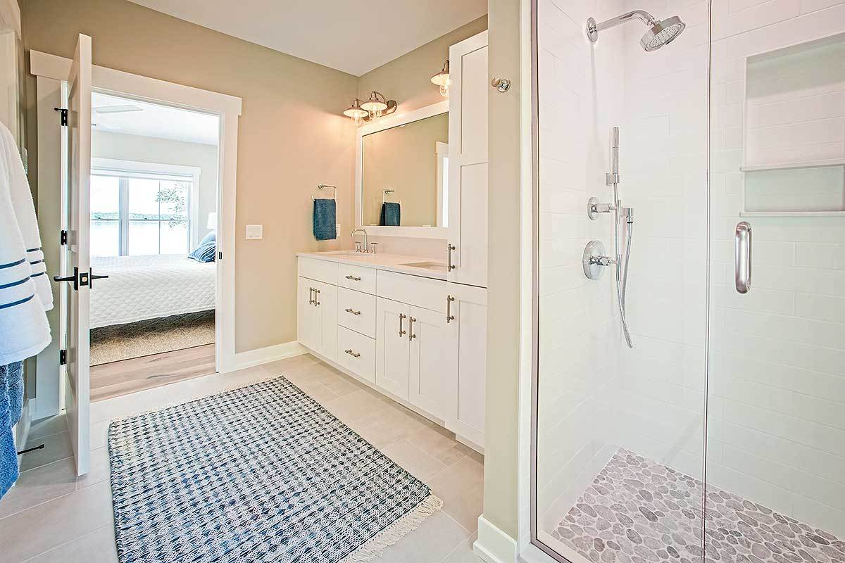 The primary bathroom has a walk-in shower and a white vanity complemented with a blue patterned rug.