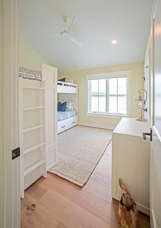 Bedroom with custom bunkbeds, light wood dresser, and white framed windows.