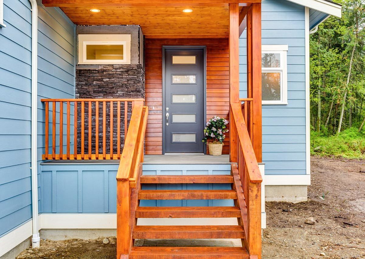 The front porch has a black entry door and wooden railings that match the staircase.