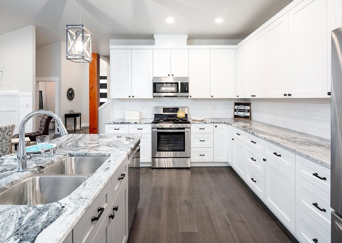 The kitchen is equipped with stainless steel appliances, granite countertops, white cabinets, and a double bowl sink fitted on the breakfast island.