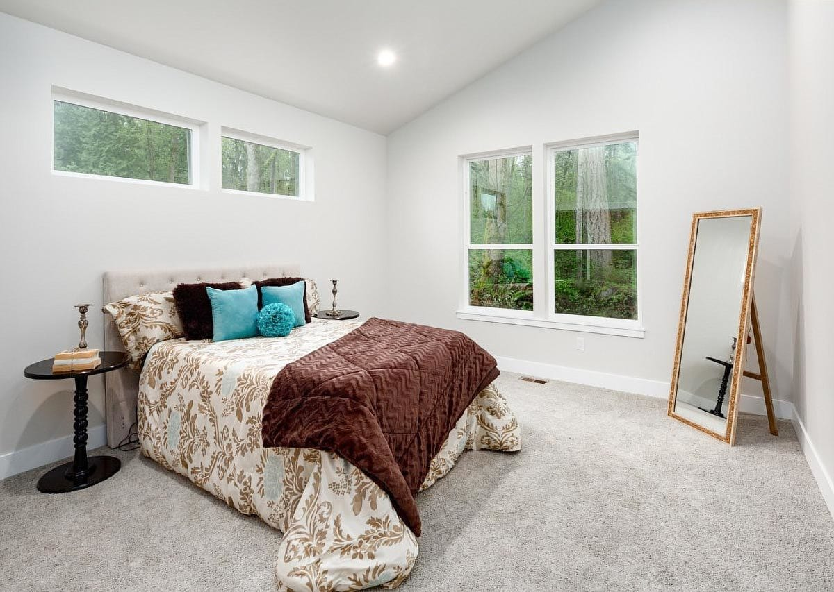 Primary bedroom with vaulted ceiling, carpet flooring, beige tufted bed, and a full-length mirror.