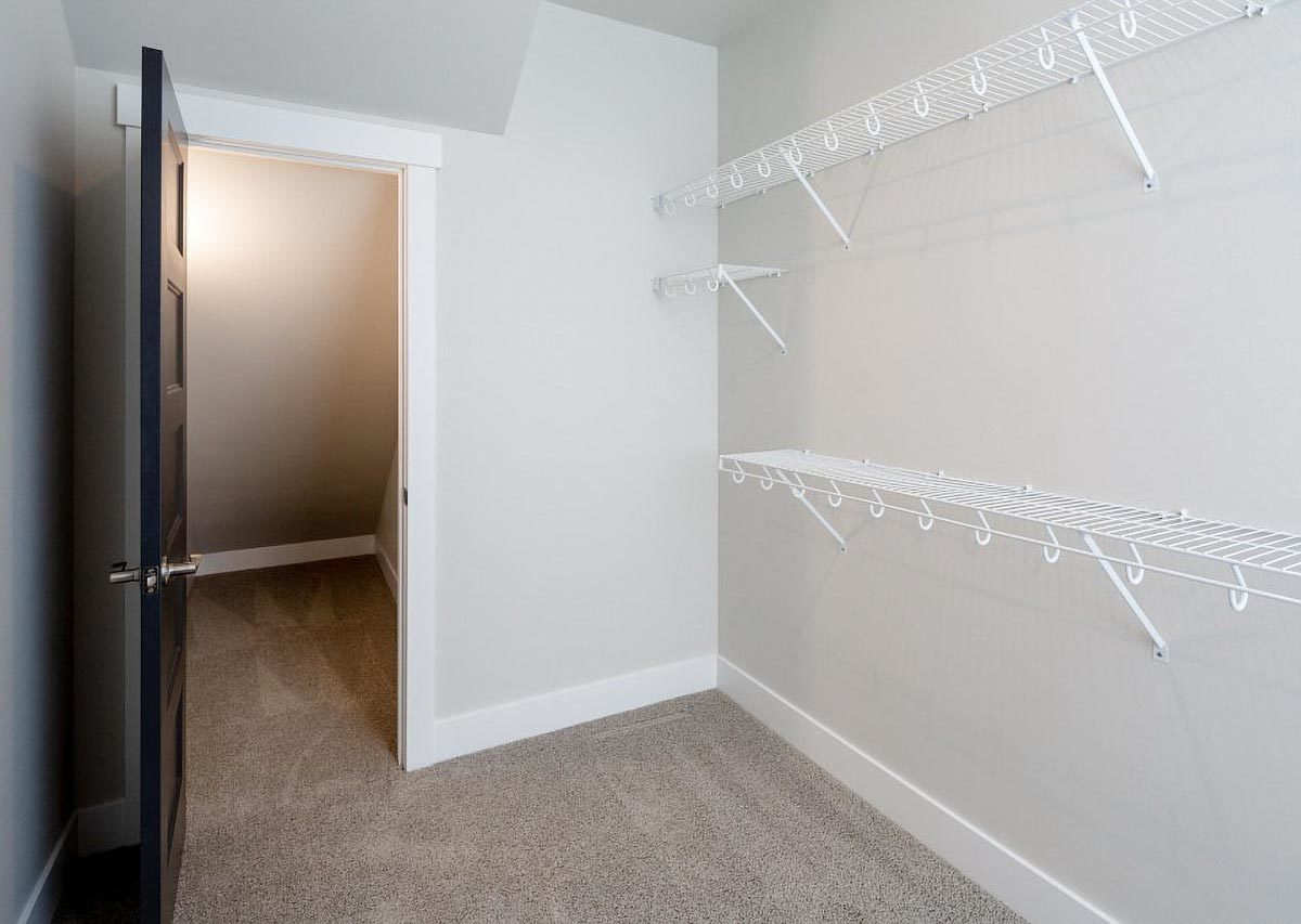 A black door opens to a spacious walk-in closet with white metal shelvings and hooks.
