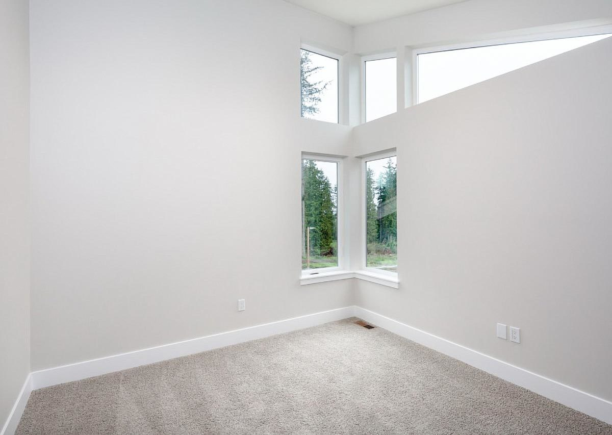 This bedroom has corner glass windows, carpet flooring, and beige walls lined with white base moldings.