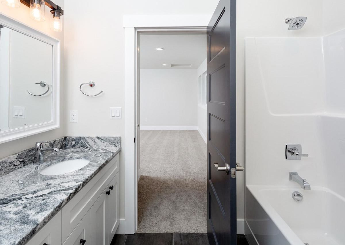 Bathroom with a granite top vanity along with a tub and shower combo.
