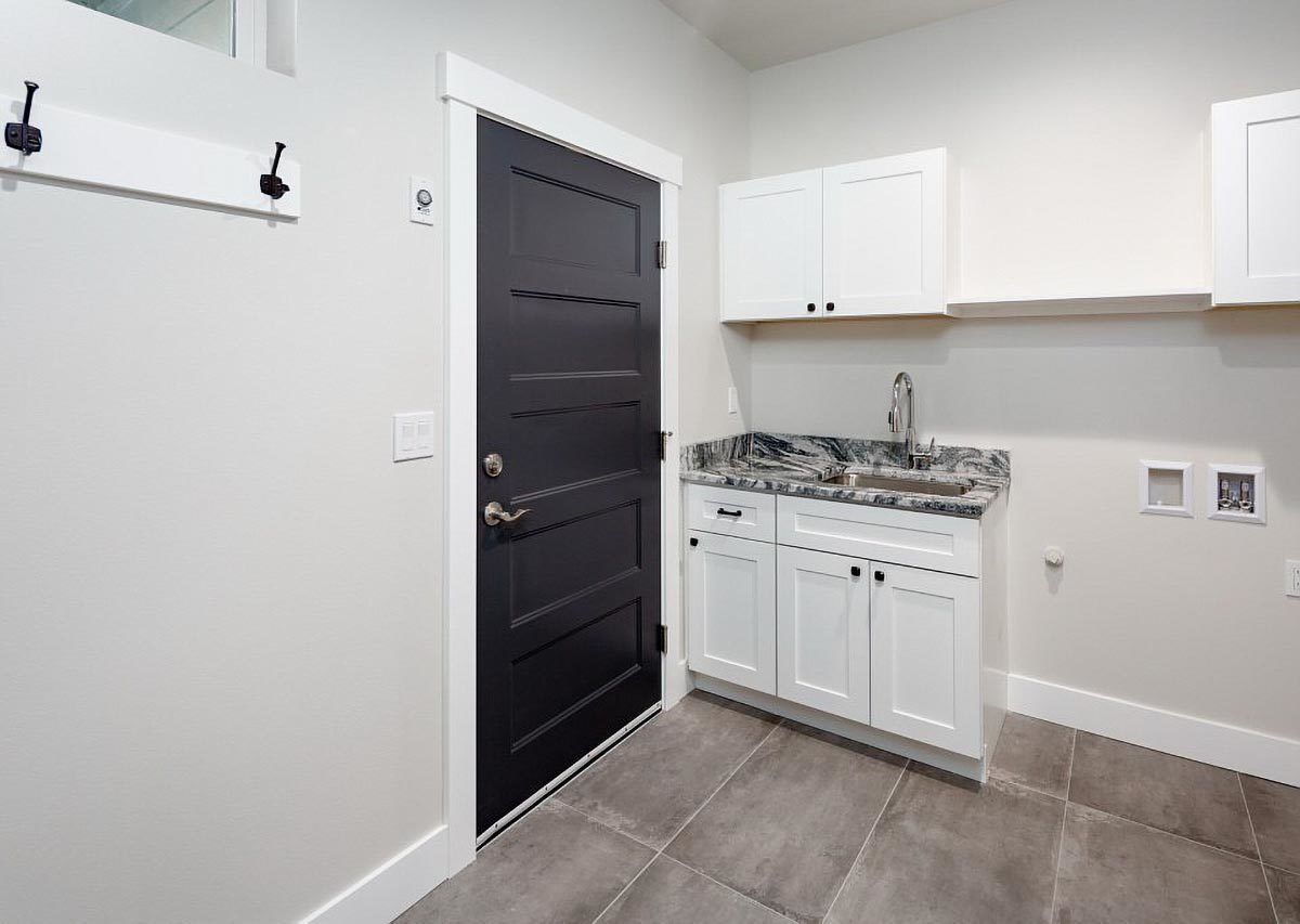 The laundry room is filled with white cabinets, undermount sink, granite countertop, and a hook rack.