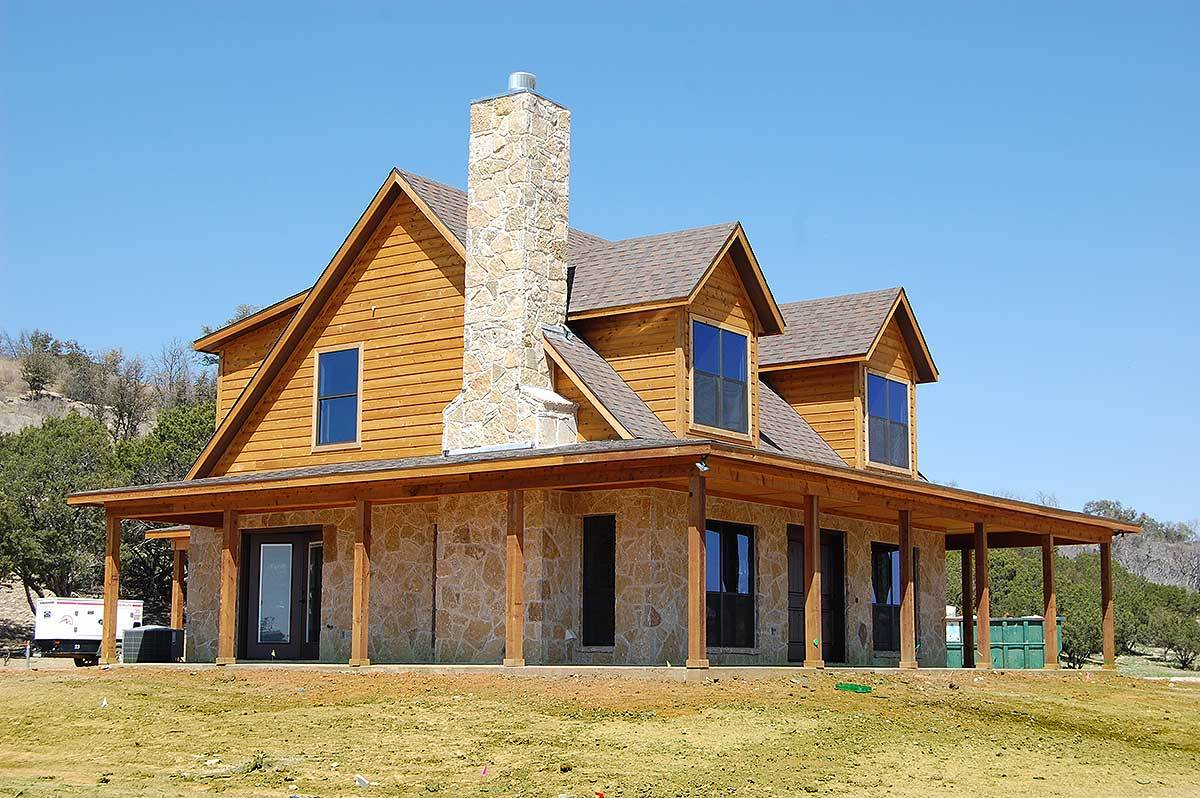 Angled side view showing the wrap-around porch, large dormers, and a stone chimney that blends in with the exterior walls.