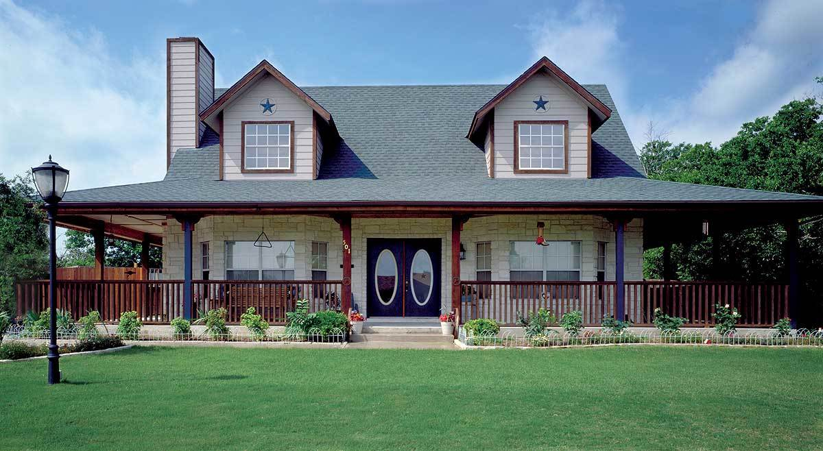 Alternate exterior with brick walls, dormer windows, a french entry door, and a wrap-around porch bordered by wooden columns and railings.