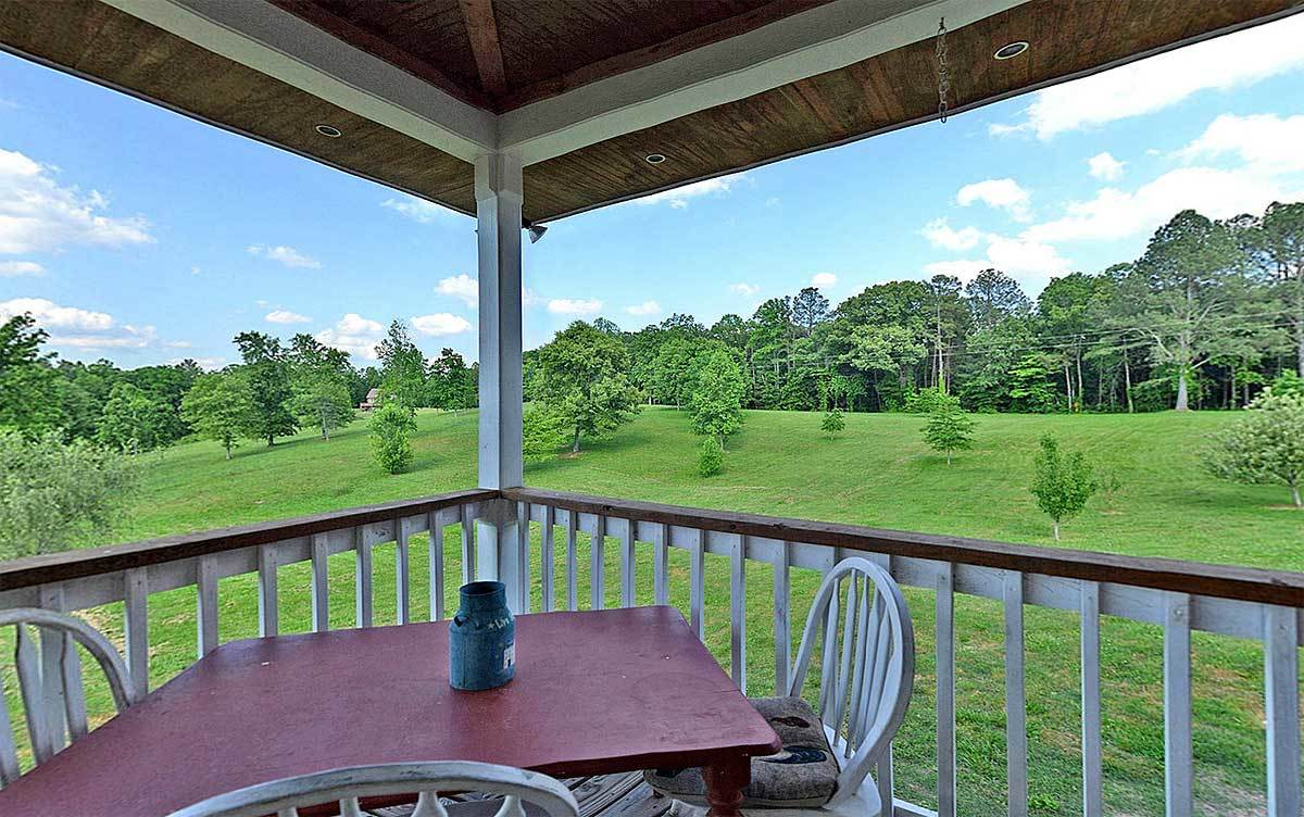 Covered porch with black rocking chairs overlooking an expansive view.