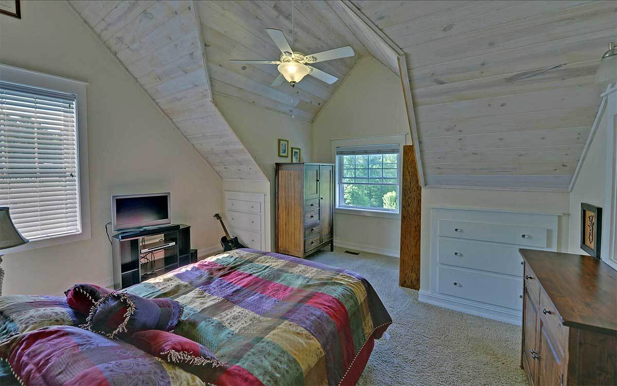 This bedroom has carpet flooring, a vaulted ceiling, and wooden furnishings.