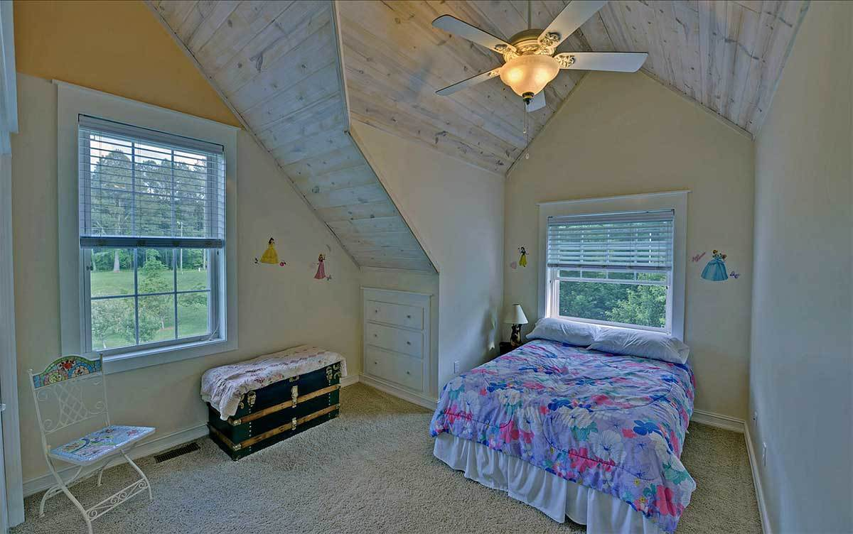 Another bedroom with a skirted bed, white metal chair, trunk chest storage, and a built-in drawer.
