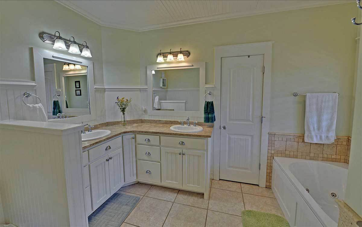Primary bath with a drop-in bathtub and a dual sink vanity paired with white framed mirrors and glass sconces.