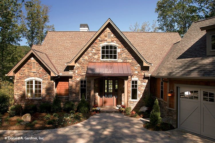 Front exterior view showing the angled garage, stone accents, and a covered entry topped with a shed roof.