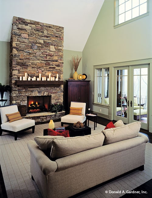 The living room has a gray sofa, white cushioned chairs, a stone fireplace, and a french door that leads out to the covered porch.