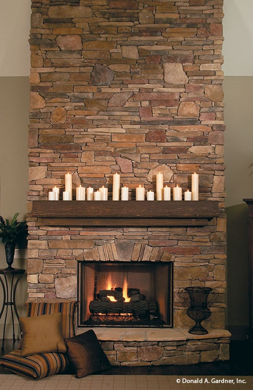 A closer look at the stone fireplace with a wooden mantel lined by white candles.