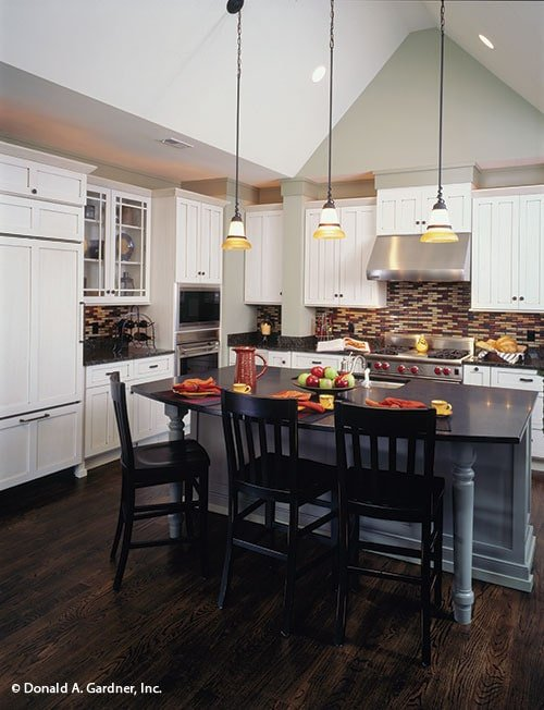 Kitchen with white cabinetry, stainless steel appliances, black granite countertops, and a breakfast island.