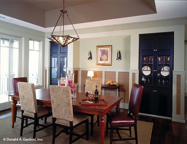 Formal dining room with black display cabinets, a rectangular dining set, and an ornate dome pendant that hangs from the tray ceiling.