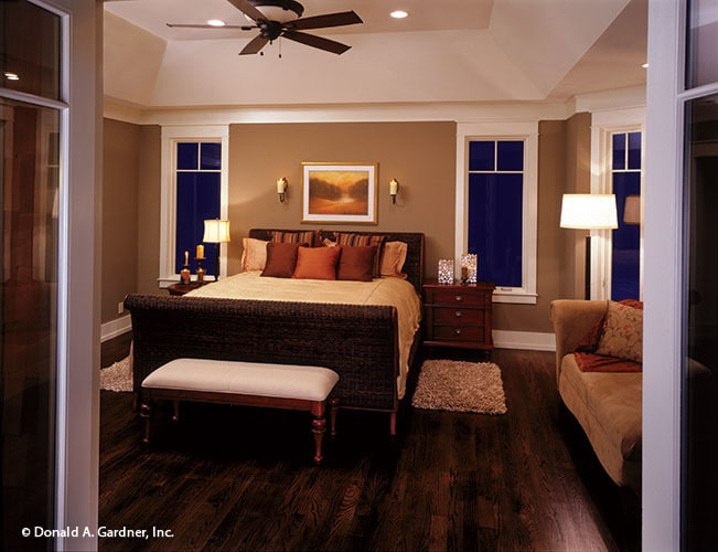 The primary bedroom has a coved ceiling, hardwood flooring, and brown walls mounted with framed artwork and sconces.